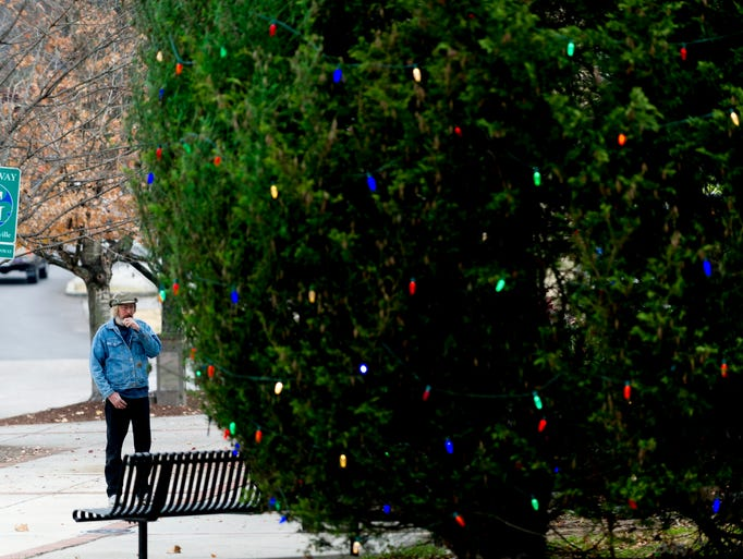 A man stands at the bus stop next to the decorated