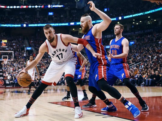 Toronto Raptors centre Jonas Valanciunas (17) protects the ball as he is defended by Detroit Pistons centre Aron Baynes (12) and Pistons forward Jon Leuer (30) during first half NBA basketball action in Toronto on Sunday, Feb.12, 2017. (Frank Gunn/The Canadian Press via AP)
