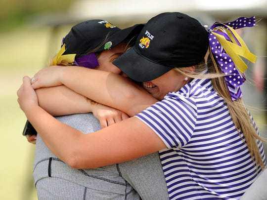 Wylie's Arin Zachary, right, hugs Kaitlyn Harbin, left, and Andrea Davis after finishing the second round of the Region I-4A tournament at Shadow Hills Golf Course in Lubbock on Thursday.