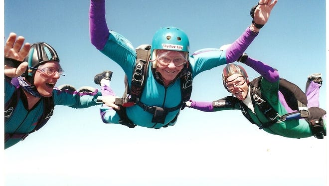Mel Potter skydiving for the first time on his 75th birthday with instructors.