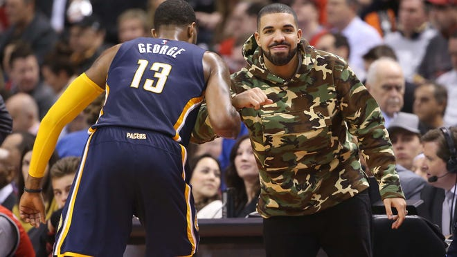 Paul George #13 of the Indiana Pacers greets recording artist Drake against the Toronto Raptors in Game One of the Eastern Conference Quarterfinals during the 2016 NBA Playoffs on April 16, 2016 at the Air Canada Centre in Toronto, Ontario, Canada.