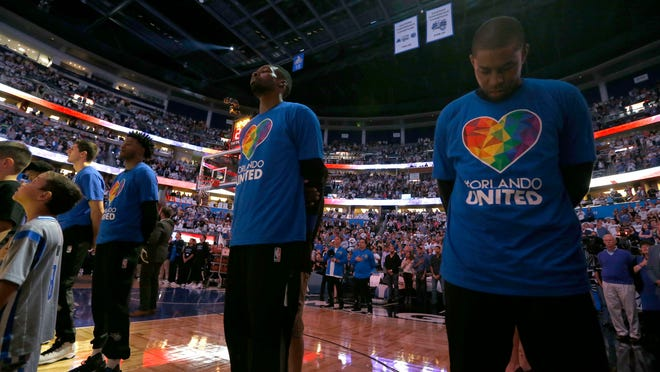 Orlando Magic forward Jeff Green (34), Orlando Magic guard C.J. Watson (32) and teammates wears an Orlando United shirt in tribute to the victims of the Pulse terror attack  during the national anthem against the Miami Heat at Amway Center.