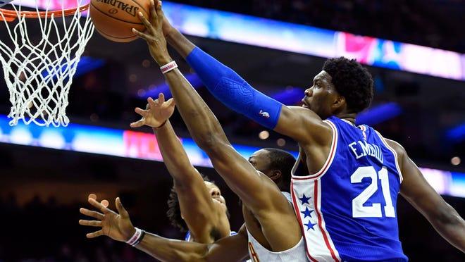 Philadelphia 76ers' Joel Embiid (21) blocks a shot taken by Atlanta Hawks' Dwight Howard, center, during the first half of an NBA basketball game, Saturday, Oct. 29, 2016, in Philadelphia.