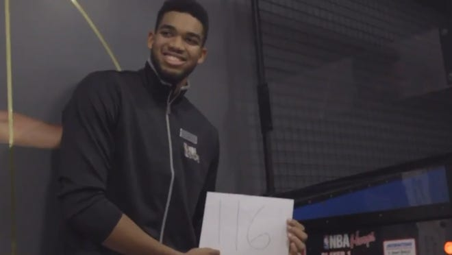 Karl-Anthony Towns posing with his Pop-a-Shot high score.