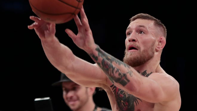 Conor McGregor shoots a basketball on the floor of Madison Square Garden while working out ahead of his UFC 205 mixed martial arts bout against Eddie Alvarez during an open workout, Wednesday, Nov. 9, 2016, in New York. McGregor will square off against Alvarez during their match on Saturday.