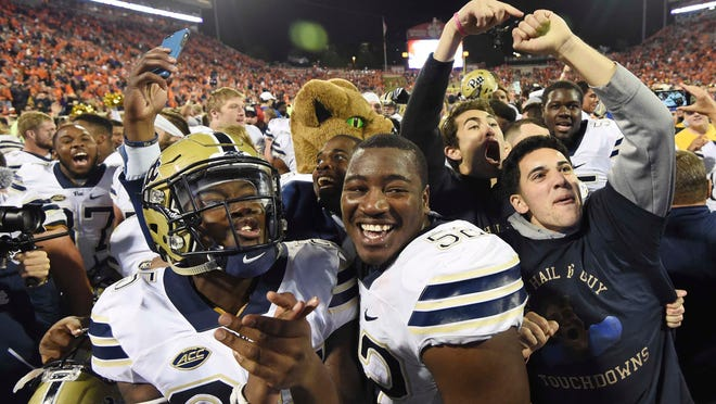 Pittsburgh's Elijah Zeise (25) and teammate Shakir Soto (52) celebrate with fans on the field after defeating Clemson 43-42 in an NCAA college football game on Saturday, Nov. 12, 2016, in Clemson, S.C. (AP Photo/Rainier Ehrhardt) ORG XMIT: SCRE120
