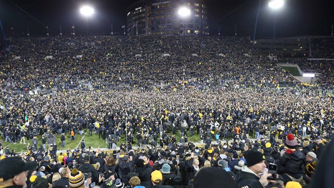 Nov 12, 2016; Iowa City, IA, USA; Fans storm the field after Iowa Hawkeyes place kicker Keith Duncan (not pictured) kicks the game winning field goal against the Michigan Wolverines at Kinnick Stadium. The Hawkeyes won 14-13. Mandatory Credit: Reese Strickland-USA TODAY Sports ORG XMIT: USATSI-270940 ORIG FILE ID:  20161112_ads_ax4_398.JPG
