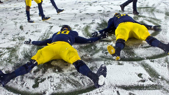 Michigan linebacker Devin Bush, left, and defensive tackle Michael Dwumfour, right, make snow angels on the Michigan Stadium field after an NCAA college football game against Indiana in Ann Arbor, Mich., Saturday, Nov. 19, 2016. Michigan won 20-10.
