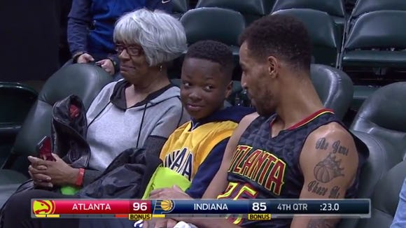 Thabo Sefolosha sits with a young Pacers fan.