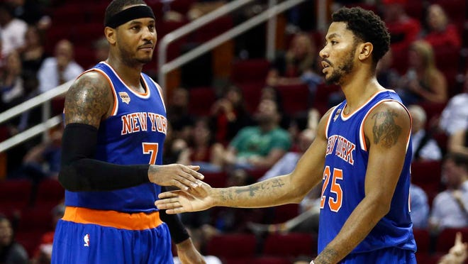 New York Knicks guard Derrick Rose (25) celebrates with forward Carmelo Anthony (7) after a play during the third quarter against the Houston Rockets at Toyota Center. The Rockets won 130-103.