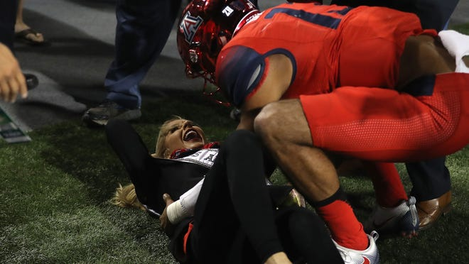 Miss Arizona USA, Tommy Lynn Calhoun is helped up by quarterback Brandon Dawkins #13 of the Arizona Wildcats after being knocked down during the second quarter of the Territorial Cup college football game against the Arizona State Sun Devils at Arizona Stadium on November 25, 2016 in Tucson, Arizona.