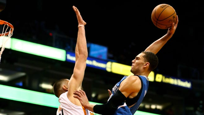 Minnesota Timberwolves guard Zach LaVine (right) goes up for a dunk over Phoenix Suns center Alex Len in the first quarter at Talking Stick Resort Arena.