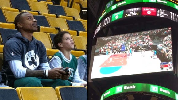 Isaiah Thomas plays video game with a young fan.