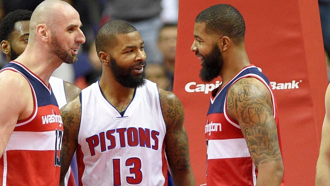 Detroit Pistons forward Marcus Morris, center, reacts with Washington Wizards forward Markieff Morris, right, during the second half of an NBA basketball game, Friday, Dec. 16, 2016, in Washington. Wizards center Marcin Gortat, of Poland, left, looks on.