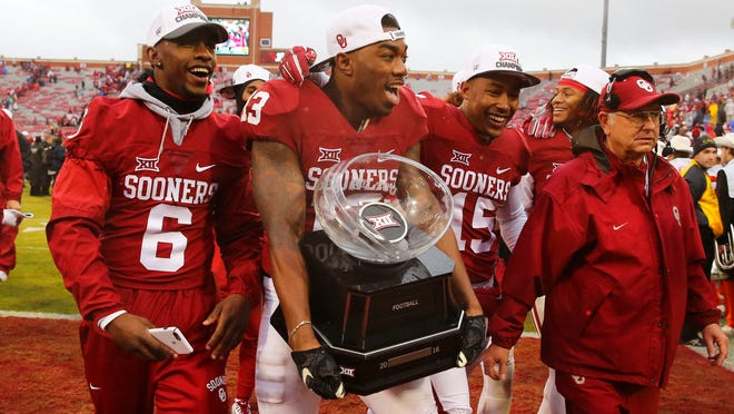Oklahoma Sooners safety Ahmad Thomas (13) runs off the field with the Big 12 championship trophy after the game against the Oklahoma State Cowboys at Gaylord Family - Oklahoma Memorial Stadium.