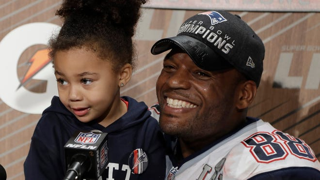 New England Patriots' Martellus Bennett appears at a news conference with his daughter Austyn Jett Rose Bennett after the NFL Super Bowl 51 football game Sunday, Feb. 5, 2017, in Houston. The New England Patriots won 34-28 in overtime.