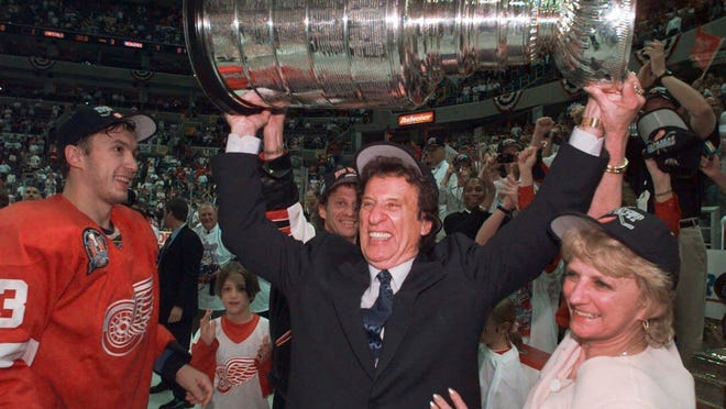 CORRECTS RED WINGS PLAYER TO VYACHESLAV KOZLOV, INSTEAD OF IGOR LARIONOV - FILE - In this June 17. 1998, file photo, Detroit Red Wings owner Mike Ilitch, center, hoists the Stanley Cup in Washington after the Red Wings won their second consecutive NHL championship. Vyacheslav Kozlov is at left. Ilitch, founder of the Little Caesars Pizza empire and owner of the Red Wings and the Detroit Tigers, has died. He was 87. Ilitch, who was praised for keeping his professional hockey and baseball teams in Detroit as other urban sports franchises relocated to new suburban stadiums, died Friday, Feb. 10, 2017, at a hospital in Detroit, according to family spokesman Doug Kuiper. (Julian H. Gonzalez/Detroit Free Press via AP) ORG XMIT: MIDTF501