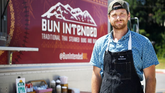 Kyle James stands next to his food truck, Bun Intended.