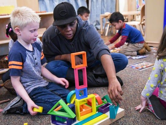 A preschool teacher helps a student build Monday, Oct.