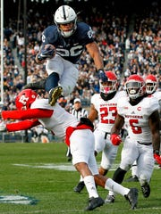 FILE - In this Nov. 11, 2017, file photo, Penn State's Saquon Barkley (26) hurdles Rutgers' Kiy Hester (2) during the second half of an NCAA college football game in State College, Pa. Despite the screams from Big Blue fans to find the replacement for Eli Manning, the Giants believe he has two or three very good years left. Helping Manning recapture the glory will be the highest-rated player in the entire draft. (AP Photo/Chris Knight, File)