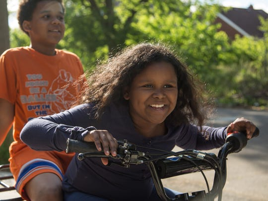 India Williams of Detroit laughs while waiting to ride her four-wheeler with her brother RJ Williams at her neighbors' house on Monday June 5, 2017, in Detroit's east side.