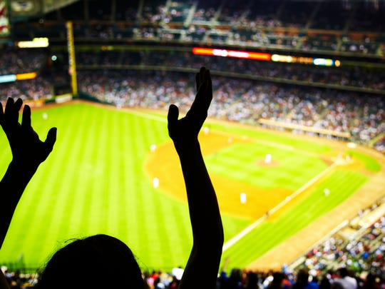 Silhouette of a person with arms raised at a baseball stadium