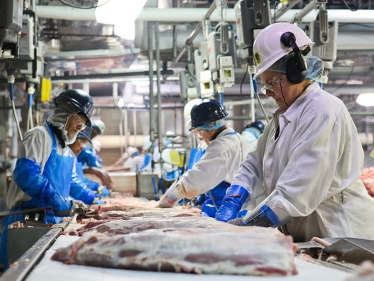 Pork products are prepped for shipment by various employees as the meat is prepped for shipment as it makes the way down conveyor belts inside Butchertown's JBS Swift pork plant earlier this year.