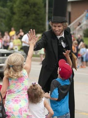 Danny Russel, dressed as Abraham Lincoln, gives high fives to children during the Greenwood Freedom Festival in 2014.