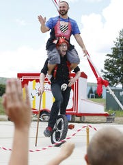 Joshua J. Superstar tries not to buckle as he rides a uni-cycle with Elmira resident Matt DeMott on his shoulders. The comedian originally asked his wife, Sora Sol, to perform the act with him, but she refused. DeMott was then chosen from the crowd and dressed similar to Sora Sol.