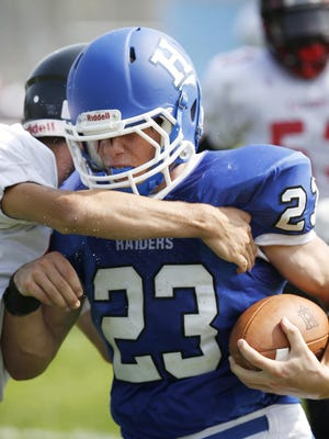 Horseheads running back Garrette Briggs shields the ball from a Fowler player Saturday.