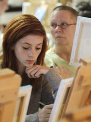 Linda Helmick works on a painting while her grandmother Kay Oliver looks for the next step during the Paint it with Pinot art class at Soho Cafe in Carmel in 2012.