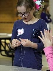 Fourth grader Ashlee Lamb works on the dental floss spider web during the Stem-A-Palooza event held for SEP TAG students.