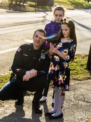 (L-R) Randolph Police Officer Richard Biase watches with Maya Kristoff, 10, as Maya's sister Kira, 8, uses a radar gun to clock motorisits on Franklin Road in Randolph. Kira's letter to the mayor brought him and the police officer to her home to check out speeders and littering.