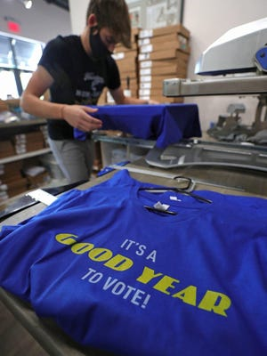 Nathan Lamos of Rubber City Clothing prints a pro-Goodyear shirt, Wednesday, Aug. 26, 2020, in Akron, Ohio. The company designed the shirts after President Trump called for a boycott of Goodyear.