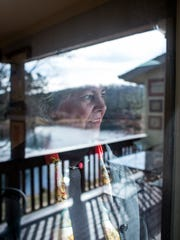Liz Colton looks out the window of her South Asheville home. The former foreign correspondent has spent her working life in newspapers, radio, television, diplomacy and more, mostly working abroad and often as the only women working overseas in the 1970s and '80s.