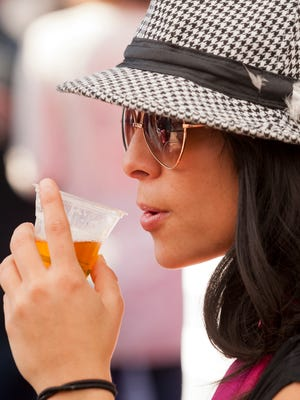 Liana Casciani, of Rochester, a graduate student at Ithaca College, tastes a sample of CoHOPeration ale fro the Hopshire Farm and Brewery, Saturday afternoon at the Ithaca Octoberfest. The ale was made from a mix of  many varieties of hops from 30 local growers.