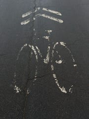 The City of Ithaca is deciding whether to install bike lanes on N. Cayuga Street after it is repaved. The street is currently marked with fading symbols indicating that the road is to be shared with bike.