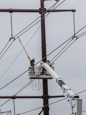 Utility workmen do some unknown work on high power electrical lines near New Castle in 2012. The Public Service Commission cleared the way Tuesday for companies other than Delmarva Power to build a power line within Delmarva's territory.