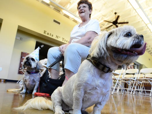Christine Eatman sits with her digs Rosie, left, and Lucy during the Celebration of Life event at the Carraige Hills Animal Hospital and Pet Resort in Montgomery, Ala. on Sunday May 4, 2014.