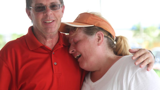 Jeff Divet hugs his wife Lauren after they won a house which was the grand prize during a miniature golf tournament held by Fucillo Kia at Mike Greenwell's on Thursday.