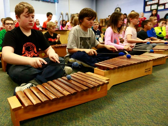 Students Aidan Alford, left, Noah Harter, Megan Nguyen, and Makenna Richmond, play xylophones Monday during a podcast recording in a music classroom at the Riverside Elementary School in Ringle.