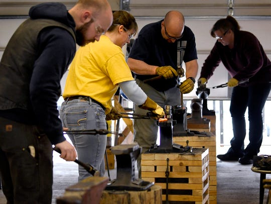 Students in a beginning blacksmith class taught by