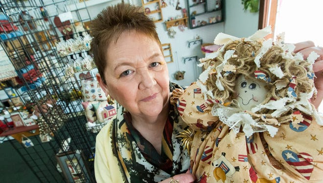 """Crafts By Arky shop owner Jennie Fowler is pictured on Thursday, March 31, 2016, with a plastic bag holder doll that she made by hand and that is available at her store, located in the Arroyo Plaza. """"This is my favorite item,"""" said Fowler."""