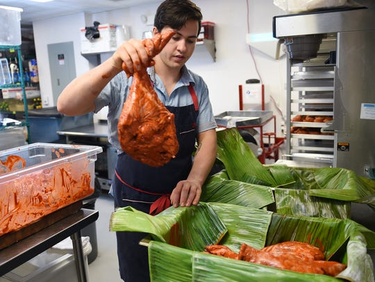 Kaelin Trilling places the pork cuts rubbed with achiote