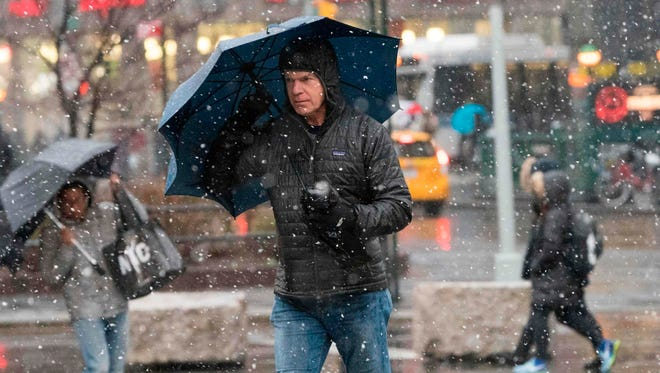 A man walks down 14th Street as heavy snow falls March 7, 2018, at Union Square in New York City.