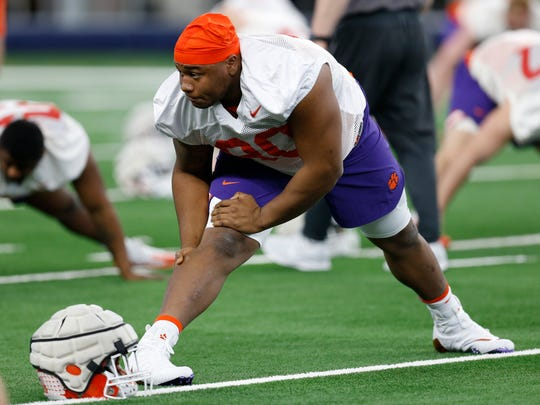 FILE - In this Dec. 24, 2018, file photo, Clemson defensive tackle Dexter Lawrence stretches during team practice at AT&T Stadium in Arlington, Texas. Clemson coach Dabo Swinney said the suspended Lawrence will be missed against top-ranked Alabama on Monday, Dec. 7, 2019. Lawrence, offensive lineman Zach Giella and tight end Braden Galloway tested positive for ostarine in NCAA drug testing. (AP Photo/Jim Cowsert, File)