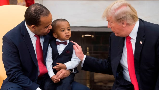 US President Donald Trump speaks about tax reform alongside Aaron Williams (L) of Topcoder in Indianapolis, Indiana, as he holds his son, during a meeting with families to discuss how the tax reform plan would affect them in the Oval Office of the White House in Washington, DC, December 5, 2017. / AFP PHOTO / SAUL LOEB        (Photo credit should read SAUL LOEB/AFP/Getty Images)