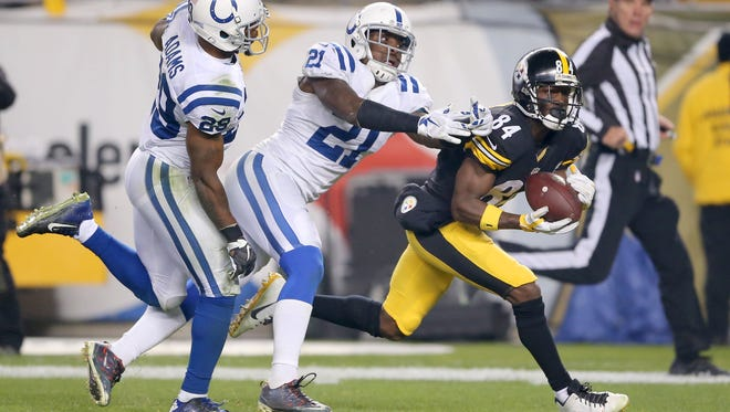 Despite the double coverage of by Indianapolis Colts strong safety Mike Adams (29) and cornerback Vontae Davis (21), Pittsburgh Steelers wide receiver Antonio Brown (84) manages to pull in a reception of a long pass to close out the third quarter of an NFL football game Sunday, Dec. 6, 2015, at Heinz Field, in Pittsburg, Pa.