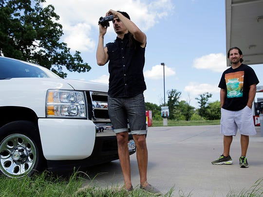 Derrick Broze, who describes himself as an activist journalist, left, with friend Mark Jankins, right, takes video at the main gate at Texas Army National Guard Camp Swift, Wednesday, July 15, 2015, in Bastrop, Texas. Jade Helm 15, a summer military training exercise that has aroused alarm among archconservative Texans, began Wednesday outside the Central Texas town of Bastrop.