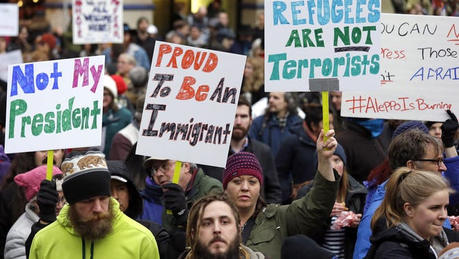 People begin to gather in Seattle on Sunday before a rally protesting President Donald Trump's travel ban on refugees and citizens of seven Muslim-majority nations.